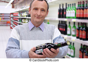 happy elderly man in shop with wine bottle in hands