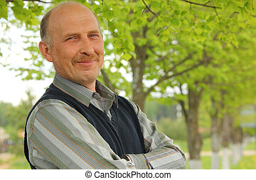 portrait of mature smiling man with crossed hands outdoor