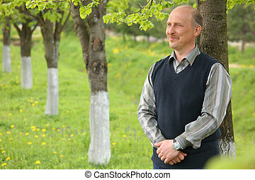 middle-aged  smiling  man in summer garden