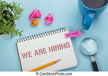 We are Hiring. Office desk table with notepad, pencil and coffee cup. Top view.