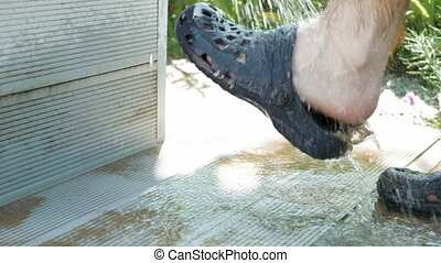 A person at the washing station to wash their feet - A...
