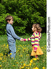 boy and girl handshaking among blossoming dandelions, focus...
