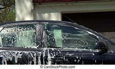 Beautiful girl washes her car with sponge - Beautiful girl...