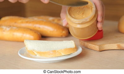 Tasty creamy peanut butter being spread on white toast.
