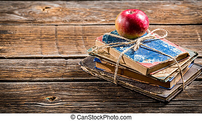 Old books and apple on school desk