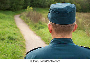 military man - officer in uniform standing back on footpath