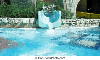 A grown woman is on waterslide in aqua park - A grown woman...