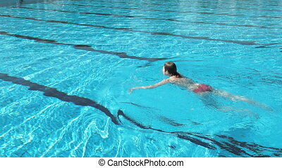 Woman is swimming in a pool on a bright summer day