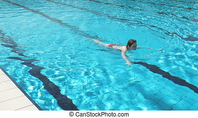Woman is swimming in a pool on a bright summer day - A woman...