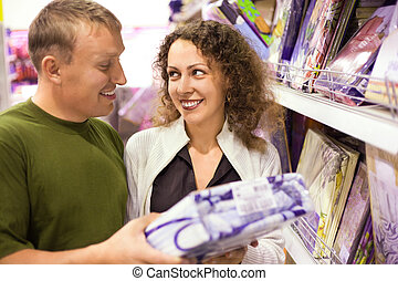 Smiling young man and woman buying bedding in supermarket, looking each other