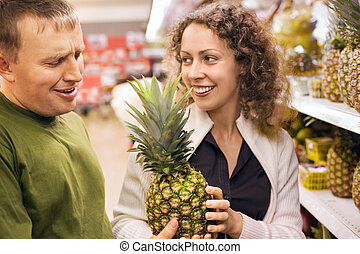Smiling young man and woman buy pineapple in supermarket