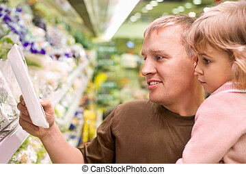 Smiling young man with little girl buy parsley in...