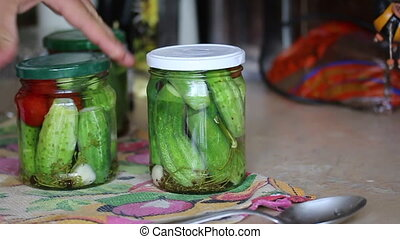 The man pickling cucumbers - The man closes the lid on cans,...