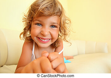 pretty smiling little girl in cosy room, stretches hands forward