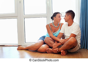 Enamoured man and woman sitting on floor near big window in cosy room