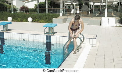 A lady in red bikini walks out of the pool