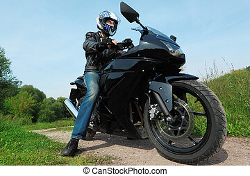 motorcyclist standing on country road, bottom view