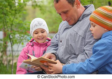father reads book for kids, focus on little girl
