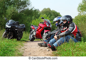 two motorcyclists sitting on country road near bikes