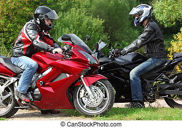 two motorcyclists standing on country road, side view, focus...