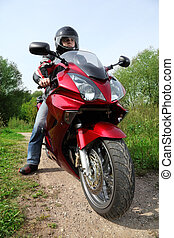 motorcyclist standing on country road, closeup