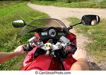 hands of motorcyclist  on country road