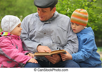 grandfather with grandchildren reads book outdoor