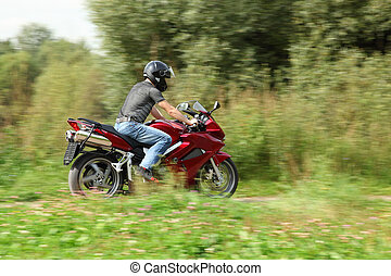 motorcyclist riding on country road, motion blur background