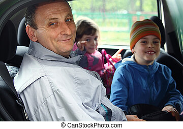 man and kids sit in the car