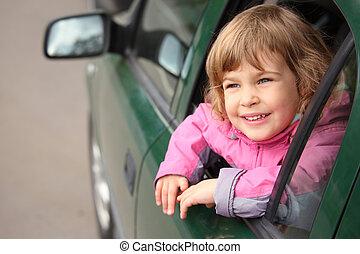 girl in the car looking throw window