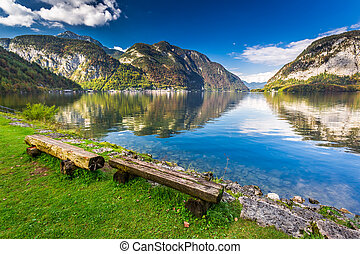 Wooden bench at mountain lake in the Alps
