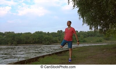 Athletic man running along sandy riverside and cruising...