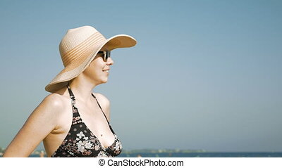 Woman standing on the beach with her fancy hat - A woman is...