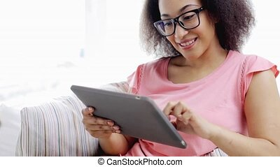 african american woman with tablet pc at home - people,...