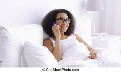african woman calling on smartphone in bed at home