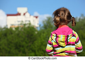 Little girl from back,  trees  and houses