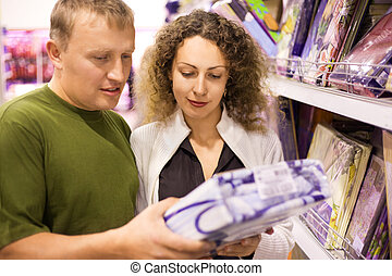 Smiling young man and woman buying bedding in supermarket,...