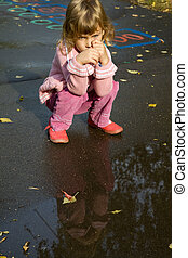 little girl sit down near pool after rain