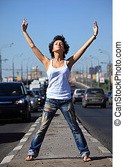 girl stands on middle of road with rised hands
