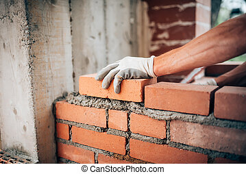 Construction worker laying bricks on exterior walls