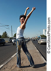 girl with lifted hands stands in half-turn on middle of road...