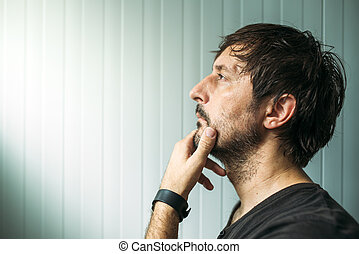 Pensive unshaven man with hand on chin making decision