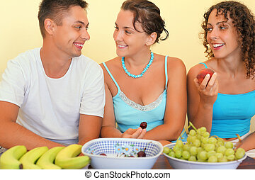 Smiling man and two young women eat fruit in cosy room