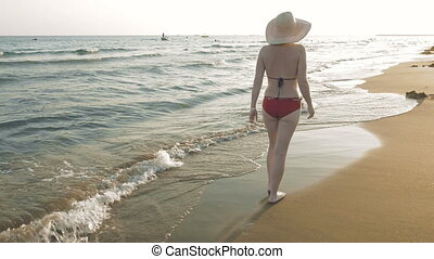A woman walking on the beach at the sunset dawn - A woman is...