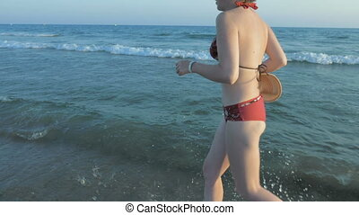 A female running in her bathing suit on the beach - A female...