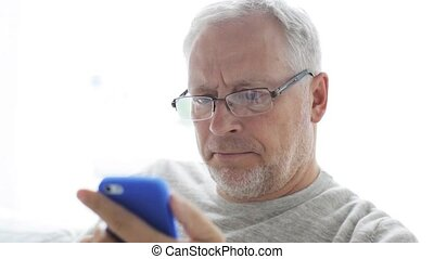 happy senior man calling on smartphone at home 130 -...