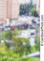 rain drops on window and blurred cityscape on background