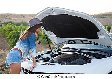 girl looks at a car engine