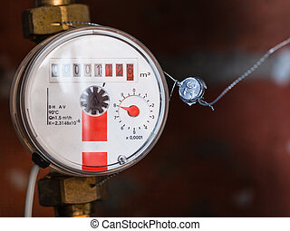 one new mechanical hot water meter on pipe close up