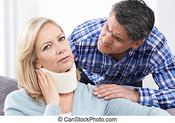 Husband Comforting wife Suffering With Neck Injury